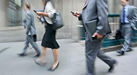 walking businessmen rushing on the street in motion blur using mobile phone
